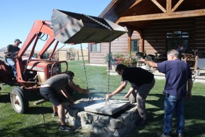 Lowering the heavy concrete lid with the help of friends and the tractors bucket